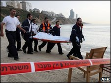 Rescue workers carry a body bag off the beach