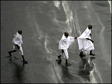 Hajj pilgrims negotiate flooded street