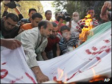 Egyptian soccer fans burn an Algerian flag in the street (November 20)