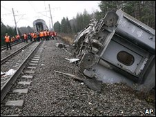 Railroad workers inspect damage coach at the site of the derailment