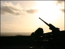 Bushes and gun at the castle silhouetted against the sky over the Channel