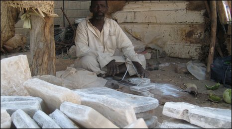 A man sits infront of piles of salt at a market in Mail