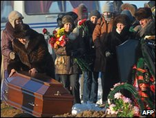 Relatives mourn over the coffin of a victim of a Russian nightclub fire outside Perm, 7 December 2009