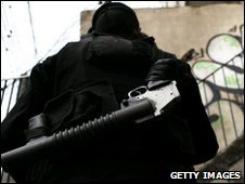 Police officer patrols Rio shanty town - file photo from 2007