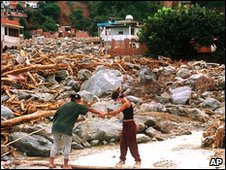Residents pick their way through debris in the town of Macuto, also hit by the floods on 21 December 1999