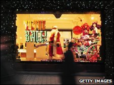 Shoppers walk past Christmas-themed window display