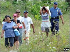 A police officer escorts residents away from the area near Mayon volcano near the town of Guinobatan in Albay province - 21 December 2009
