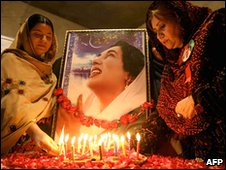 Supporters light candles in front of a picture of slain former PM Benazir Bhutto