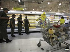 Soldiers check prices in a Caracas supermarket