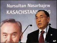 Kazakh Foreign Minister Kanat Saudabayev in front of an image of Kazakh President Nursultan Nazarbayev