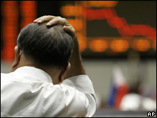 Stockbroker with his hand on his head (Image: AP)