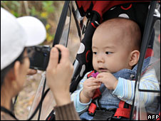 South Korean woman takes a photo of her baby sitting on a pushchair, April 2009