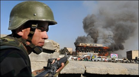 An Afghan National Army (ANA) soldier keeps watch as smoke billows from a building