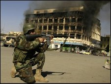 An Afghan police officer aims his weapon at the scene of attack in central Kabul
