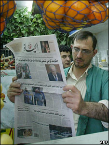 A fruit juice seller reads a newspaper in Damascus. File photo