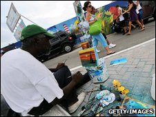 A street painter works on a painting to sell to tourists