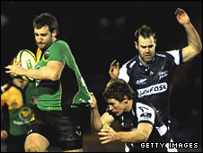 Northampton's Chris Mayor is tackled by David Bishop and Charlie Hodgson of Sale