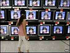 A woman looks at televisions on display in Wuhan, central China