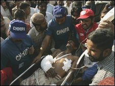 An injured person is helped after the Karachi blast, 5 February, 2010