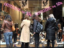 Women look at the discounted prices in front of a shopwindow at a shoe shop in central Athens