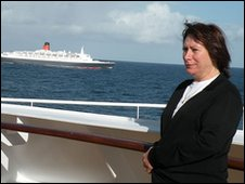 The woman seen posing on the QM2 with the QE2 in the background