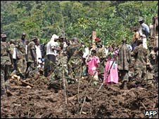 Ugandan villagers and soldiers stand on fresh earth following a landslide. Photo: 2 March 2010
