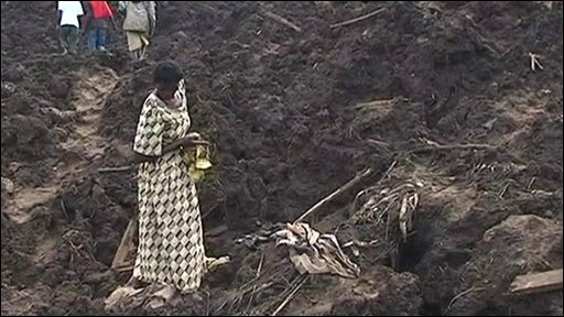 A woman searches for belongings in Bududa, Uganda, after a landslide