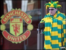 A man sells green and yellow scarves outside Old Trafford