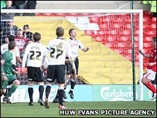 Luke Chambers (far right) heads into an empty net after an error from Dorus de Vries (far left)