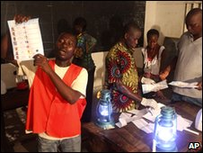 An election official displays a ballot as votes are counted in Lome on 4 March