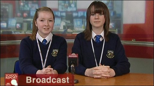 Two students in front of a news desk