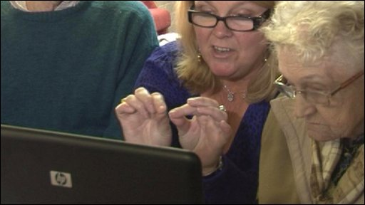 Maxine Bowler teaches two pensioners to use a laptop