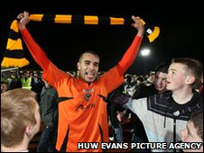 Paul Bignot waves the County scarf with joy after the final whistle