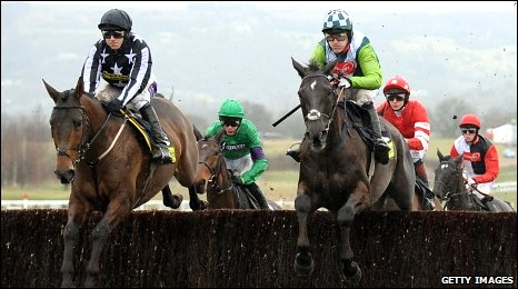 Imperial Commander (left) and Denman clear the first fence during Friday's Gold Cup