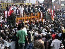 """Nepali Congress party leaders and supporters throng to catch a glimpse of former Prime Minister Girija Prasad Koirala as his body is taken to the stadium on a truck covered with flowers and party""""s red and white flags, in Katmandu, Nepal, Sunday, March 21, 2010"""
