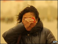 A woman wipes sand from her eyes as she walks in Beijing on 20 March 2010