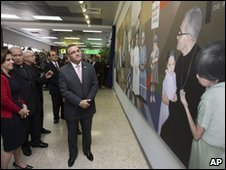 President Mauricio Funes (centre) stands by the mural of Archbishop Romero at El Salvador airport
