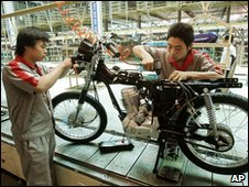 Workers assembling a motorbike in China