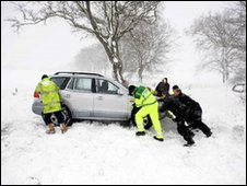 Motorists try to dig out vehicles from heavy snow on the A702 road south of Edinburgh