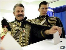 Hungarians in traditional uniform vote in general elections