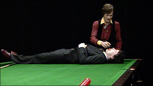 Alex Higgins prepares to perform a trick shot with Jimmy White