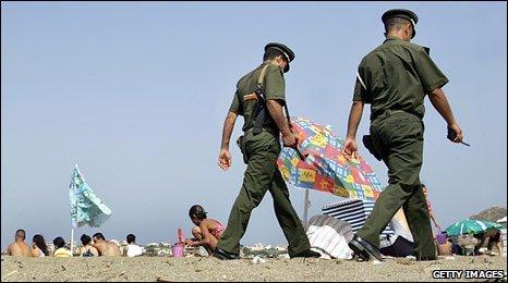Algerian policemen patrol a beach