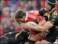 Munster's Ronan O'Gara is tackled by Paul James and Ian Gough