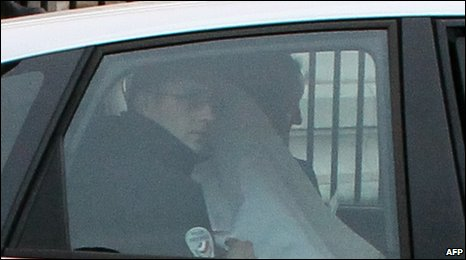 Manuel Noriega, draped in a white sheet, leaves a Paris court on 27 April