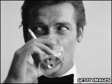 James Bond actor Roger Moore with a drink and a cigarette