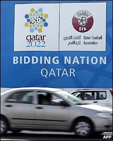 Car passing Qatar bid poster in Doha