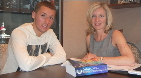 Footballer Raddy Majewski and English tutor Liz Nathan sit in the Nottingham Forest Football Club boardroom