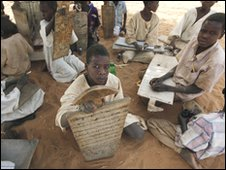 Sudanese refugee children hold their writing boards