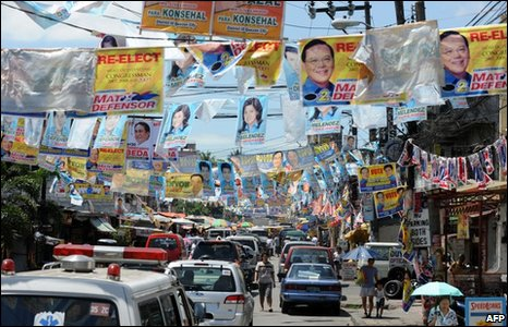 Posters of election candidates hang over a road in Manila on 6 May 2010