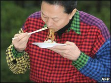 Japanese Prime Minister Yukio Hatoyama eats noodles in a many-coloured shirt, 4 April